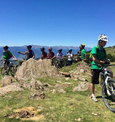 Grup de joves equipats amb les seves bicis i casc en un prat observant el Cadí de fons.