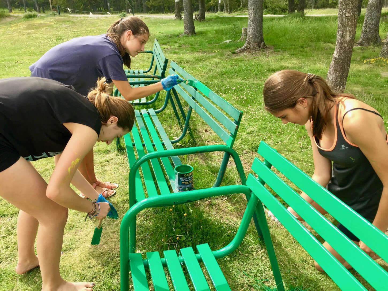 Noies de les colònies repintant de verd els bancs del campament.