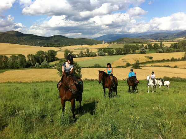 Un petit grup de nois i noies muntant a cavall per un extens prat
