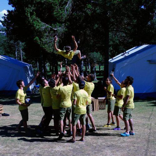 Monitors del campament agrupats llançant a un d'ells a l'aire